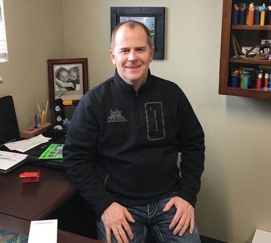 Photo of Dave Huston sitting on his desk.
