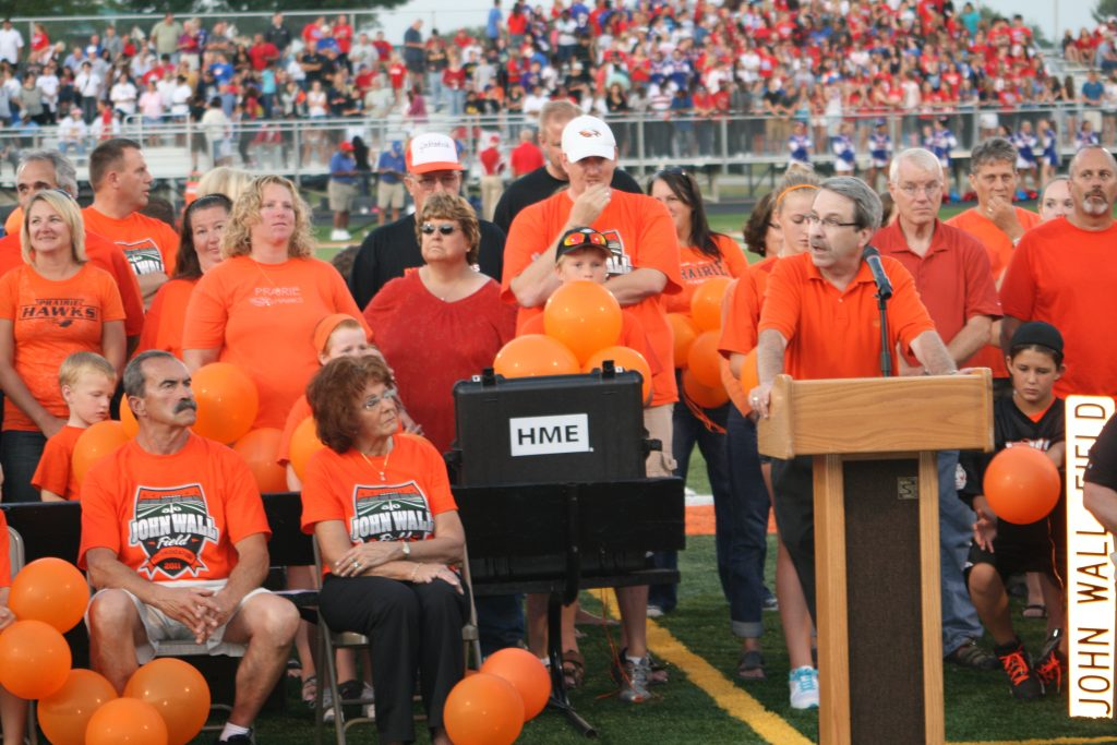 School Board President Randy Bauer standing behind a podium speaking to an audience at the John Wall rededication event.