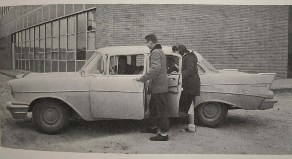 Two students in 1959 getting into a four door car.