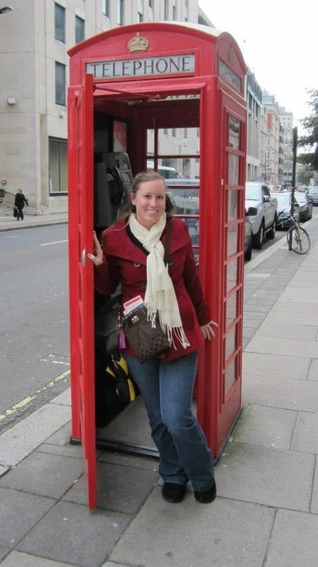 Photo of Kylee Erenberger Koziesek standing in front of a phone booth in New York City